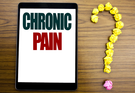 Word, writing Chronic Pain. Business concept for Feeling Bad ill Care Written on tablet, background with question mark on the end. Foto de archivo