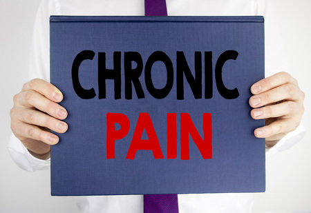 Writing text showing Chronic Pain. Business concept for Feeling Bad ill Care written on book notebook paper holding by man in suit blurred background.