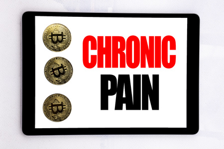 Writing text showing Chronic Pain. Business concept for Feeling Bad ill Care written on tablet screen on white background with cryptocurrency bitcoin next to it. Foto de archivo