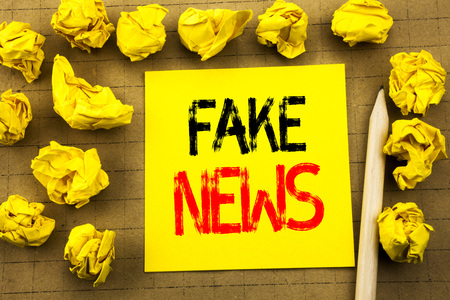 Fake News. Business concept for Hoax Journalism written on sticky note paper on vintage background. Folded yellow papers on the background