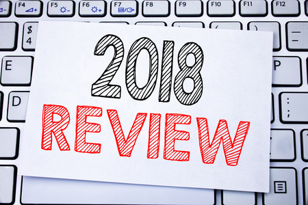 Handwritten text caption showing 2018 Review. Business concept writing for Feedback On Progress written on sticky note paper on white keyboard background. Banco de Imagens