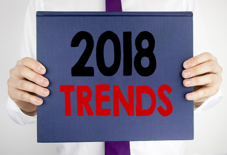 Writing text showing 2018 Trends. Business concept for Trending Data Prediction written on book notebook paper holding by man in suit blurred background.