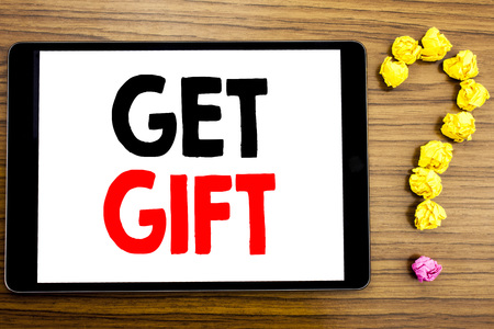 Writing text showing Get Gift. Business concept for Free Shoping Coupon written on tablet computer on wooden background with question mark made of folded paper.