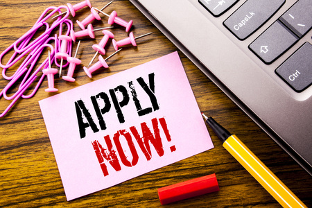 Handwritten text showing Apply Now. Business concept for Job Hiring Application  written on pink sticky note paper on wooden background next to keyboard. With red pen.