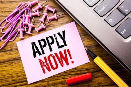 Texto escrito a mano que muestra Aplicar ahora. Concepto de negocio para la solicitud de contratación de empleo escrita en papel de nota adhesiva rosa sobre fondo de madera junto al teclado. Con bolígrafo rojo.