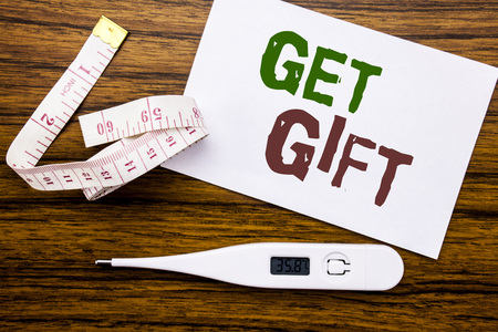 Conceptual hand writing text caption showing Get Gift. Business concept for Free Shoping Coupon written on sticky note paper wood background. Meter and thermometer for fitness subject.