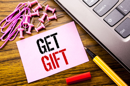 Handwritten text showing Get Gift. Business concept for Free Shoping Coupon written on pink sticky note paper on wooden background next to keyboard. With red pen. Stock Photo