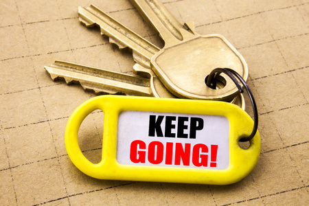 Word, writing Keep Going. Business concept for Go Moving Forward Letting Written on key holder, close up.