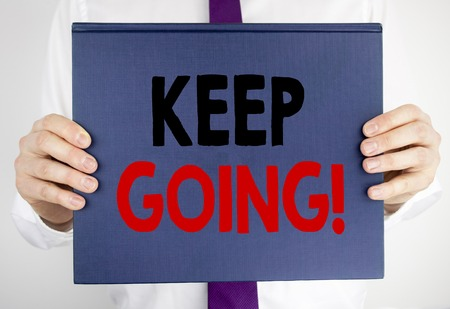 Writing text showing Keep Going. Business concept for Go Moving Forward Letting written on book notebook paper holding by man in suit blurred background.