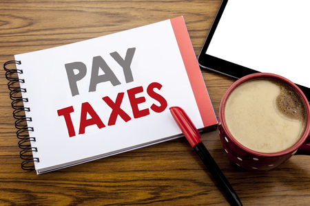 Handwriting Announcement text showing Pay Taxes. Business concept for Taxation Overtax Return Written on notepad paper on wooden background with space office view with pencil marker