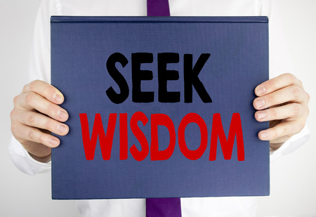 Writing text showing Seek Wisdom. Business concept for Inspiration Knowledge written on book notebook paper holding by man in suit blurred background.
