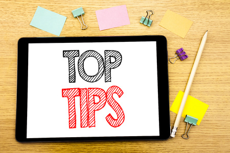 Writing text showing Top Tips. Business concept for Expert Tip Guidance Written on tablet, wooden background with sticky note and pen