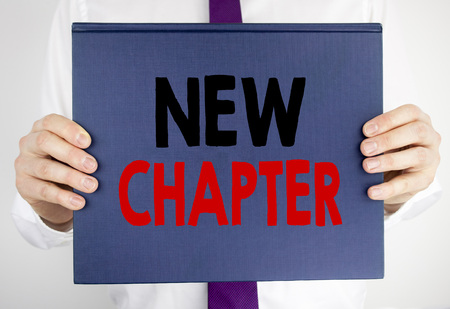 Writing text showing New Chapter. Business concept for Starting New Future Life written on book notebook paper holding by man in suit blurred background.