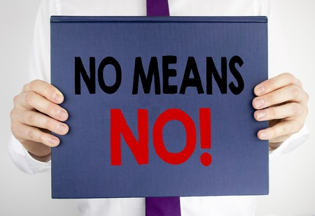Writing text showing No Means No. Business concept for Stop Anti Rape Slogan written on book notebook paper holding by man in suit blurred background. Stock Photo