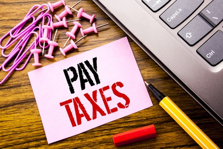 Handwritten text showing Pay Taxes. Business concept for Taxation Overtax Return written on pink sticky note paper on wooden background next to keyboard. With red pen.
