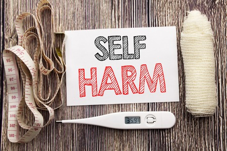 Handwritten text showing Self Harm. Business fitness health concept writing for Selfharm Mental Aggression written on wood wooden background with bandage and thermometer     Stock Photo