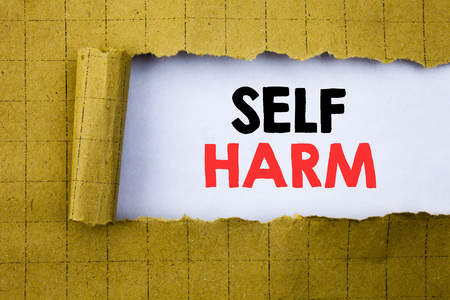 Self Harm. Business concept for Selfharm Mental Aggression written on white paper on yellow folded paper.