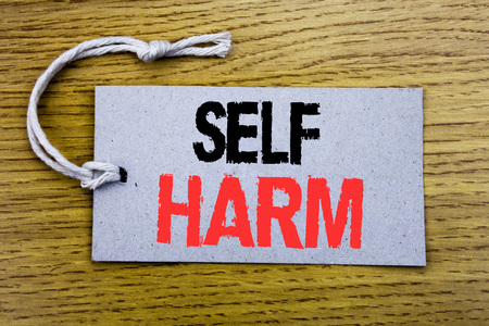 Conceptual hand writing text caption showing Self Harm. Business concept for Selfharm Mental Aggression written on price tag paper with copy space on wooden vintage background