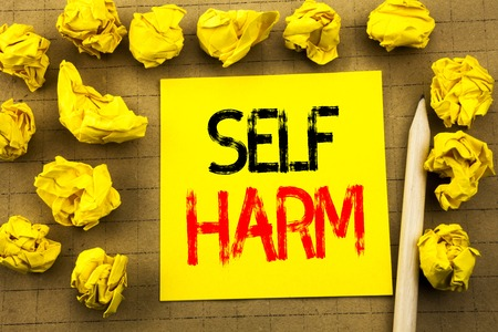 Self Harm. Business concept for Selfharm Mental Aggression written on sticky note paper on vintage background. Folded yellow papers on the background Stock Photo