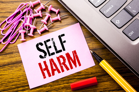 Handwritten text showing Self Harm. Business concept for Selfharm Mental Aggression written on pink sticky note paper on wooden background next to keyboard. With red pen. Stock Photo