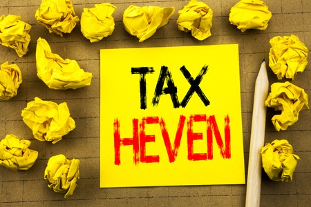 Tax Heven. Business concept for Profit Taxation  written on sticky note paper on vintage background. Folded yellow papers on the background
