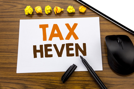 Conceptual hand writing text showing Tax Heven. Business concept for Profit Taxation  written on sticky note paper on wooden background with marker mouse and tablet office view.