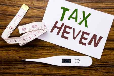 Conceptual hand writing text caption showing Tax Heven. Business concept for Profit Taxation  written on sticky note paper wood background. Meter and thermometer for fitness subject. Stock Photo