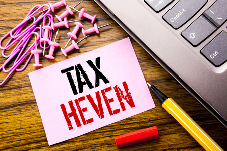 Handwritten text showing Tax Heven. Business concept for Profit Taxation  written on pink sticky note paper on wooden background next to keyboard. With red pen.