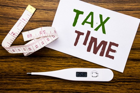 Conceptual hand writing text caption showing Tax Time. Business concept for Taxation Finance Reminder written on sticky note paper wood background. Meter and thermometer for fitness subject. Stock Photo