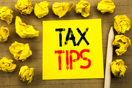 Tax Tips. Business concept for Tip Forn Taxes written on sticky note paper on vintage background. Folded yellow papers on the background