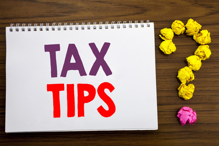 Conceptual hand writing caption inspiration showing Tax Tips. Business concept for Tip Forn Taxes written on notepad paper on the wooden background with question mark.