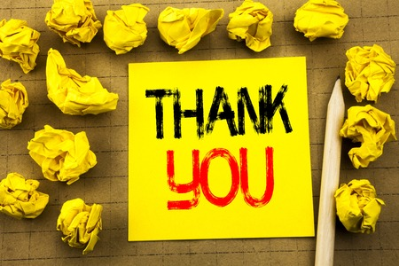 Thank You. Business concept for Gratitude Thanks written on sticky note paper on vintage background. Folded yellow papers on the background