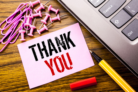 Handwritten text showing Thank You. Business concept for Gratitude Thanks written on pink sticky note paper on wooden background next to keyboard. With red pen.
