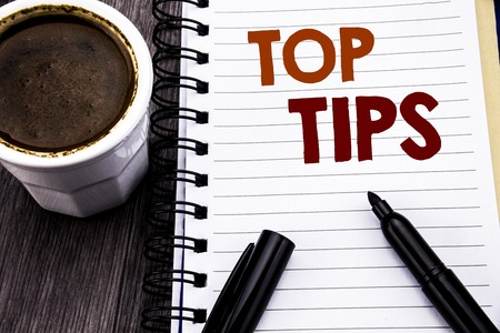 Writing text showing Top Tips. Business concept for Expert Tip Guidance written on notebook book note paper on wooden wood background. With coffee and black marker.