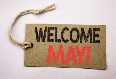 Hand writing text caption inspiration showing Welcome May. Business concept for Hello Month Greeting written on price tag paper on white vintage background.