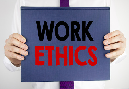 Writing text showing Work Ethics. Business concept for Moral Benefit Principles written on book notebook paper holding by man in suit blurred background. 스톡 콘텐츠