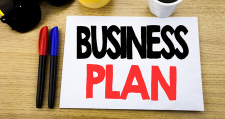 Handwritten text caption showing Business Plan. Business concept writing for Mission or Vision written on sticky note with copy space old wood wooden background with sunglasses