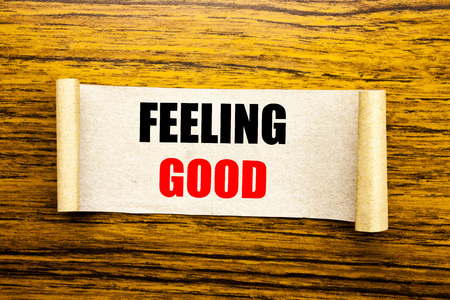 Hand writing text caption inspiration showing Feeling Good. Business concept for Happy Positive Attitude written on sticky note paper on wooden background.