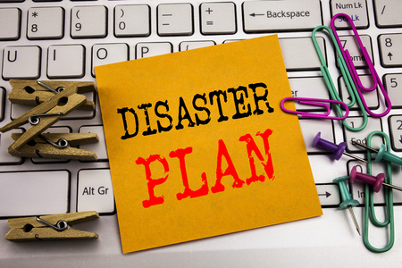 Writing text showing Disaster Plan. Business concept for Emergency Recovery written on sticky paper on the white keyboard background.