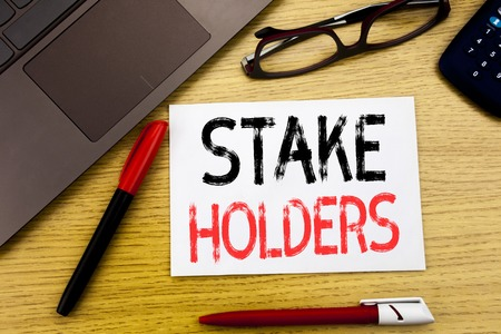 Conceptual hand writing text showing Stake Holders. Business concept for Stakeholder Engagement written on paper, wooden background in office copy space, marker pen and glasses