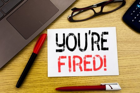 Conceptual hand writing text showing You Are Fired. Business concept for Unemployed or Discharge written on paper, wooden background in office copy space, marker pen and glasses Stock Photo