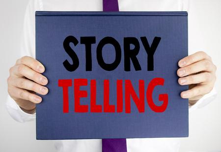 Redacción de texto mostrando narración de cuentos. Concepto de negocio para Teller Story Mensaje escrito en papel de cuaderno libro sosteniendo por hombre en traje fondo borroso. Foto de archivo