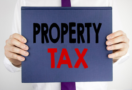 Writing text showing Property Tax. Business concept for Estate Income Taxation written on book notebook paper holding by man in suit blurred background.
