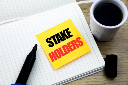 Hand writing text caption inspiration showing Stake Holders. Business concept for Stakeholder Engagement written sticky note paper, Wooden background with copy space, Coffee and marker Banque d'images