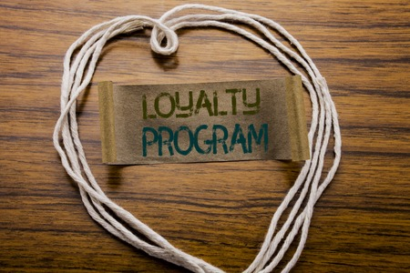 Conceptual hand writing text caption Loyalty Program. Business concept for Marketing Concept written on sticky note paper on dark wooden background. With heart meaning love or adoration.