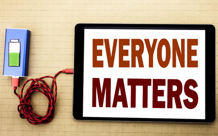 Hand writing text caption inspiration showing Everyone Matters. Business concept for Equality Respect written on tablet laptop with white textured background with mobile charger power bank