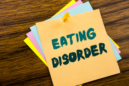 Hand writing text caption inspiration showing Eating Disorder. Business concept for Medical Problem written on sticky note paper on wooden background.