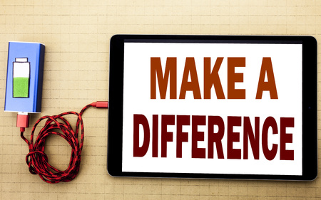 Hand writing text caption inspiration showing Make A Difference. Business concept for Motivation Success written on tablet laptop with white textured background with mobile charger power bank