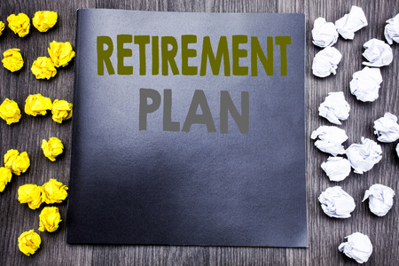 Hand writing text caption inspiration showing Retirement Plan. Business concept for Pension Finance Written on notepad note notebook wooden background with sticky folded yellow and white 免版税图像