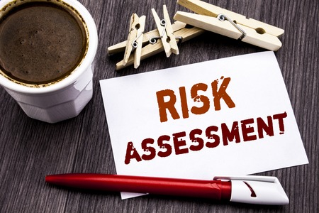 Hand writing text caption inspiration showing Risk Assessment. Business concept for Safety Danger Analyze written on sticky note paper on wooden wood background. With coffee and red pen.